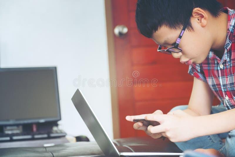 Gioco sveglio del gioco del ragazzo nel telefono cellulare ed esaminare il computer portatile, fotografia stock libera da diritti