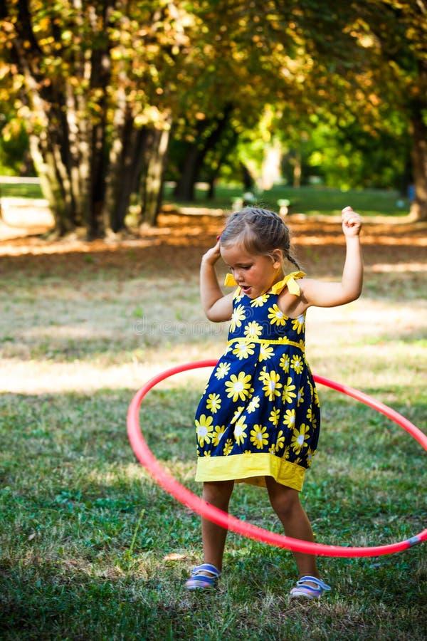 Gioco sveglio della bambina con il hula-hoop in parco immagini stock libere da diritti
