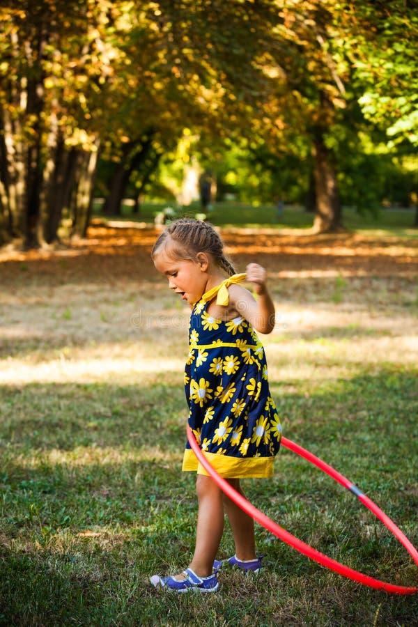 Gioco sveglio della bambina con il hula-hoop in parco fotografie stock libere da diritti