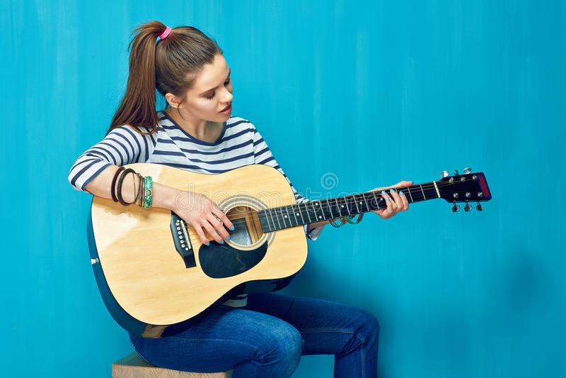 Gioco teenager della ragazza con divertimento sulla chitarra fotografia stock