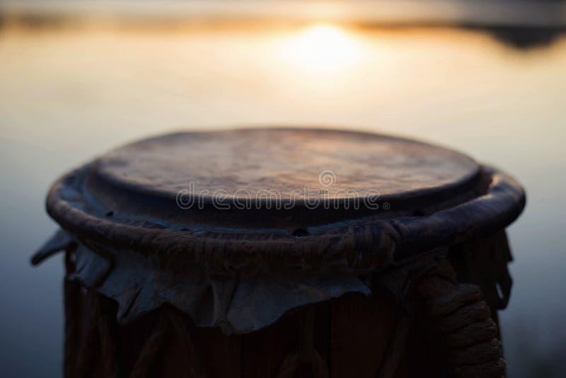Gioco un jembe o del atabaque dello strumento musicale sul cielo del fondo al tramonto immagini stock