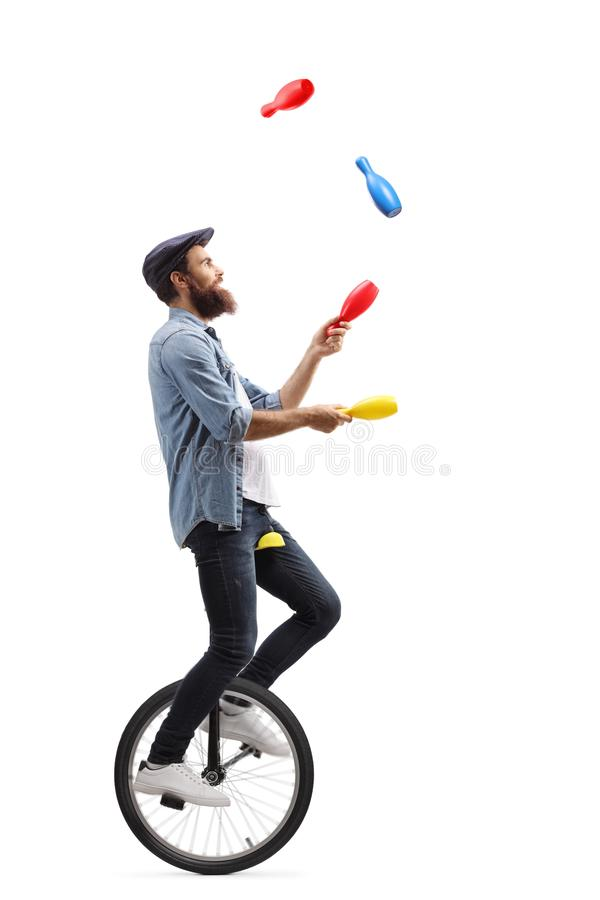 Giocoliere maschii su un monociclo che manipolano con i club fotografia stock libera da diritti