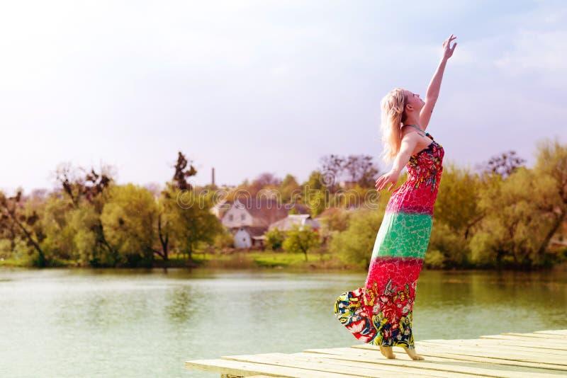 Gioia di dancing: bella giovane donna esile bionda chegode dell'allungamento in vestito leggero lungo nel lago dell'acqua su verd fotografia stock