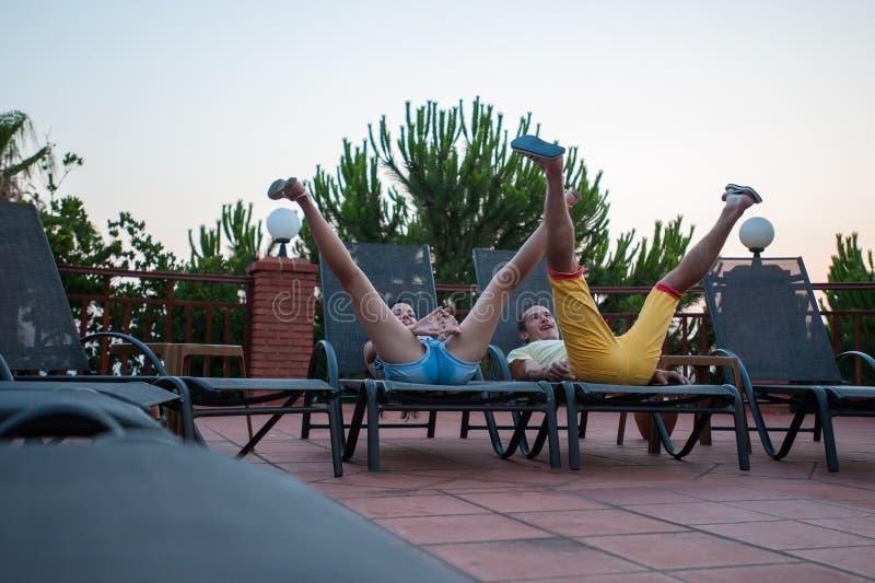 Gioia sulla vacanza insieme Concetto di feste, di vacanza, di amore e di amicizia - coppia sorridente divertendosi in amaca immagine stock