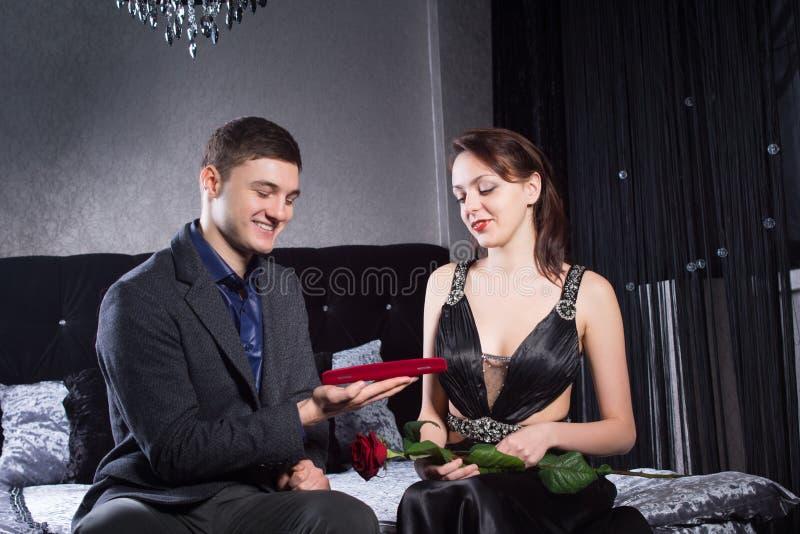 Gioielli d'offerta dell'uomo in scatola rossa alla donna immagini stock