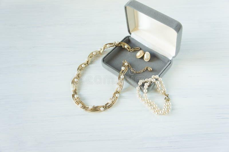 Gioielli del ` s della donna Fondo d'annata dei gioielli Bei oro e collana ed orecchini della perla in un contenitore di regalo s immagini stock libere da diritti