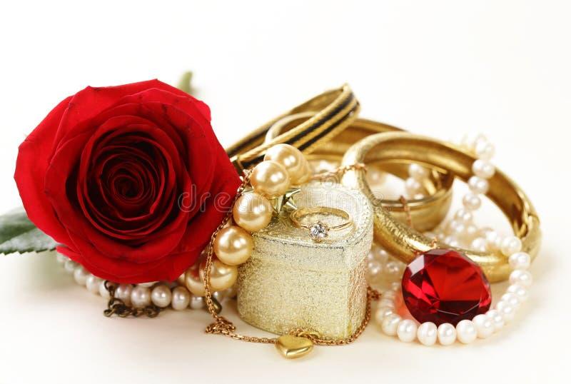 Gioielli dell'oro (perle, collana, anello) con le rose fotografia stock