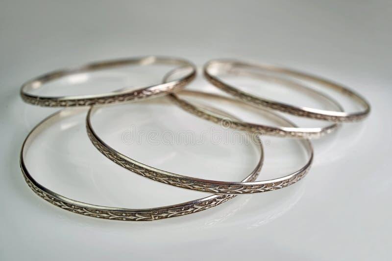 Gioielli femminili - argento, vecchi braccialetti su un fondo bianco fotografie stock libere da diritti