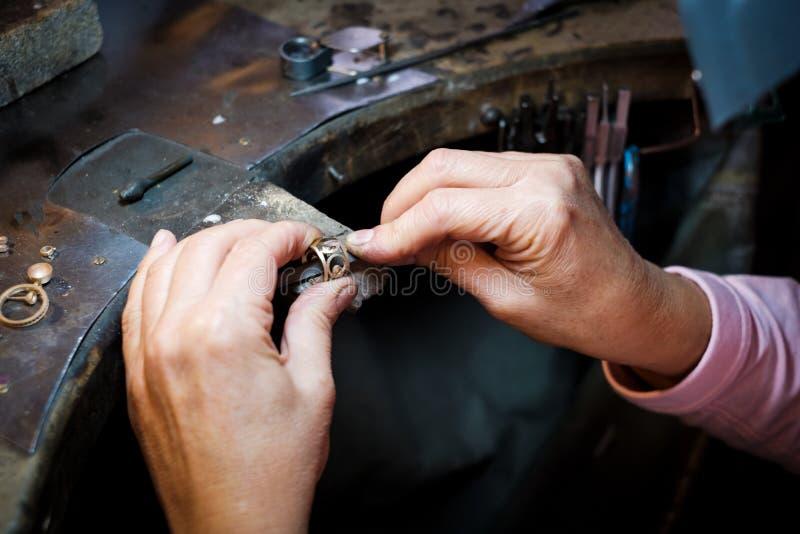 Gioielliere che lavora con l'anello di oro dell'archivio dell'ago nell'officina dei gioielli fotografie stock