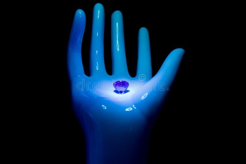 Gioiello del diamante nel palmo di una mano su fondo nero immagini stock libere da diritti