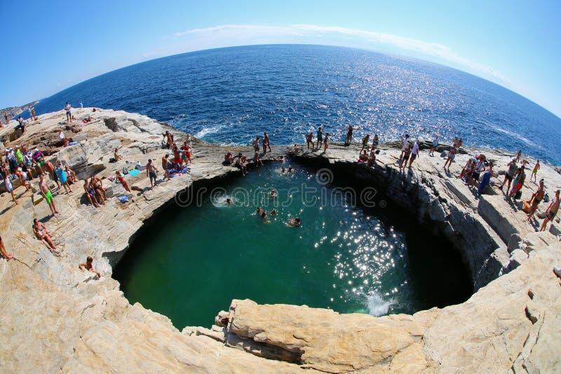 GIOLA, THASSOS, GRECIA - AGOSTO DE 2015: Turistas que se bañan en el Giola Giola es una piscina natural en la isla de Thassos, Se fotos de archivo libres de regalías