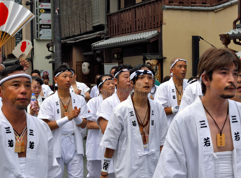 Gion Matsuri parade 1. KYOTO, JAPAN - July 24, 2017: A group of men parade down a street in Kyoto, Japan yelling and chanting, as a part of the Gion Festival royalty free stock photo