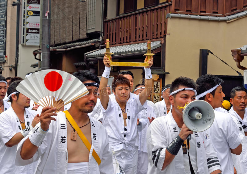 Gion Matsuri parade 2. KYOTO, JAPAN - July 24, 2017: A group of men--one of whom is holding a sacred object made of brass--parade down a street in Kyoto, Japan stock photo