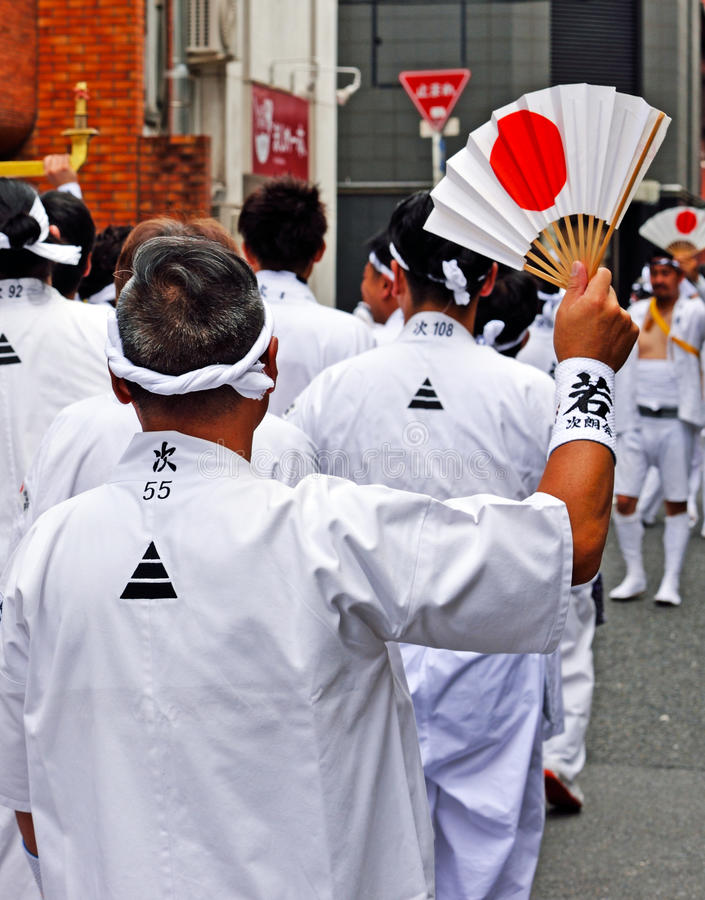 Gion Matsuri parade 3. KYOTO, JAPAN - July 24, 2017: A man waves a white fan with a rising sun on it, as a member of a group of men parade down a street in Kyoto stock photo