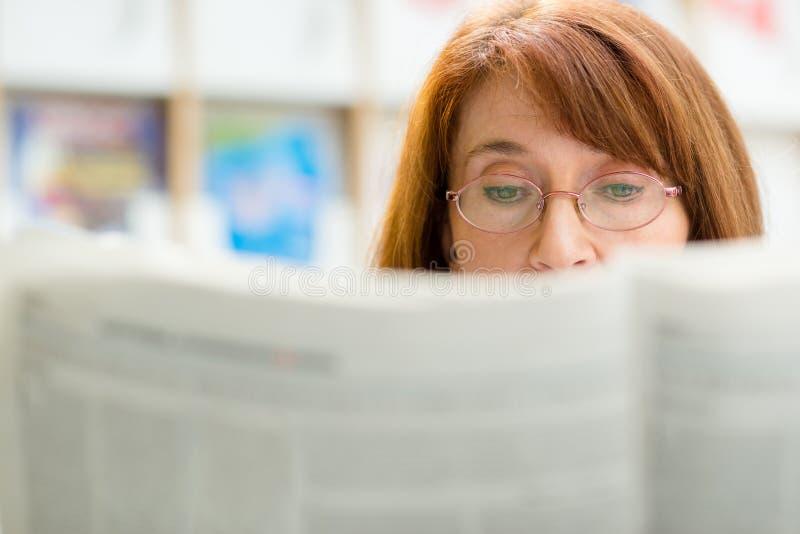 Giornale anziano della lettura della donna in libreria fotografia stock libera da diritti