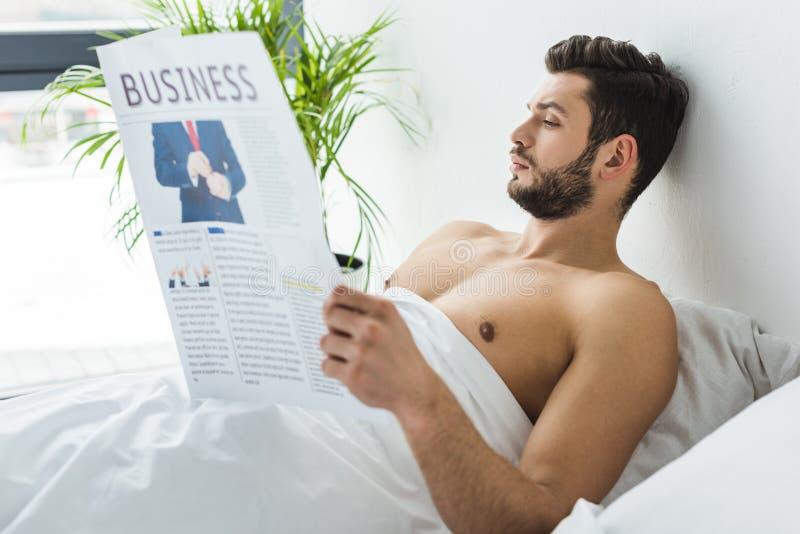 giornale barbuto senza camicia di affari della lettura dell'uomo a letto immagine stock libera da diritti