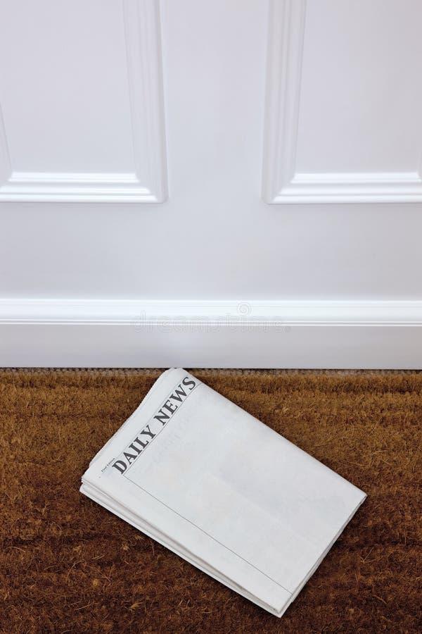 Giornale in bianco che si trova su un doormat. immagini stock