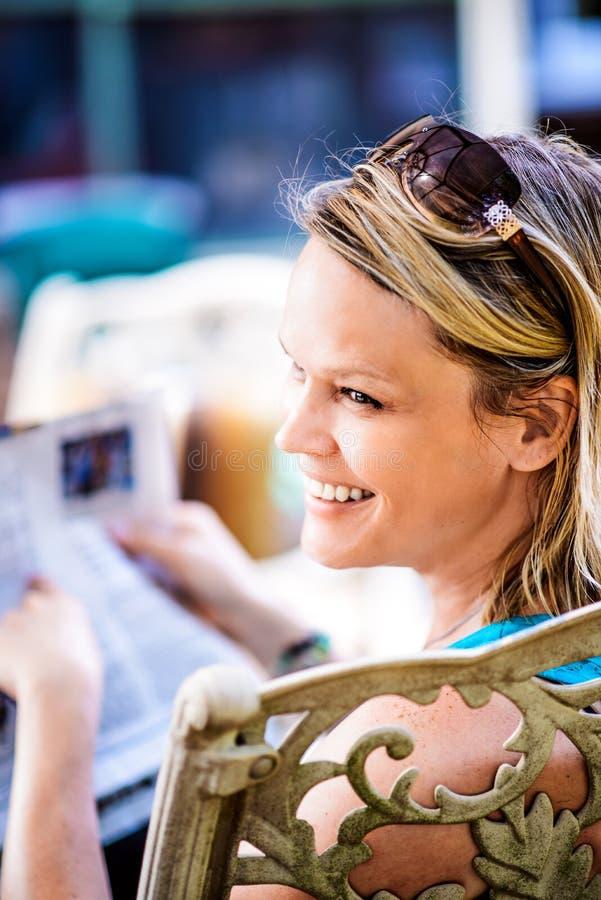 Giornale biondo sorridente della lettura della donna all'aperto fotografia stock libera da diritti