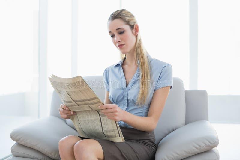 Giornale calmo serio della lettura della donna di affari che si siede sullo strato fotografia stock
