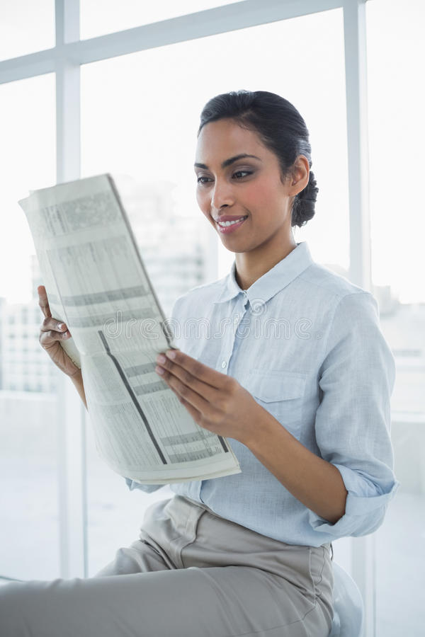 Giornale calmo sorridente adorabile della lettura della donna di affari fotografia stock