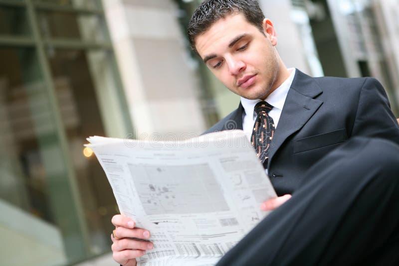 Giornale della lettura dell'uomo di affari fotografia stock