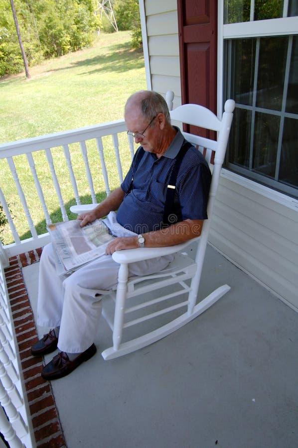 Giornale della lettura dell'uomo maggiore sul portico di fronte immagine stock libera da diritti
