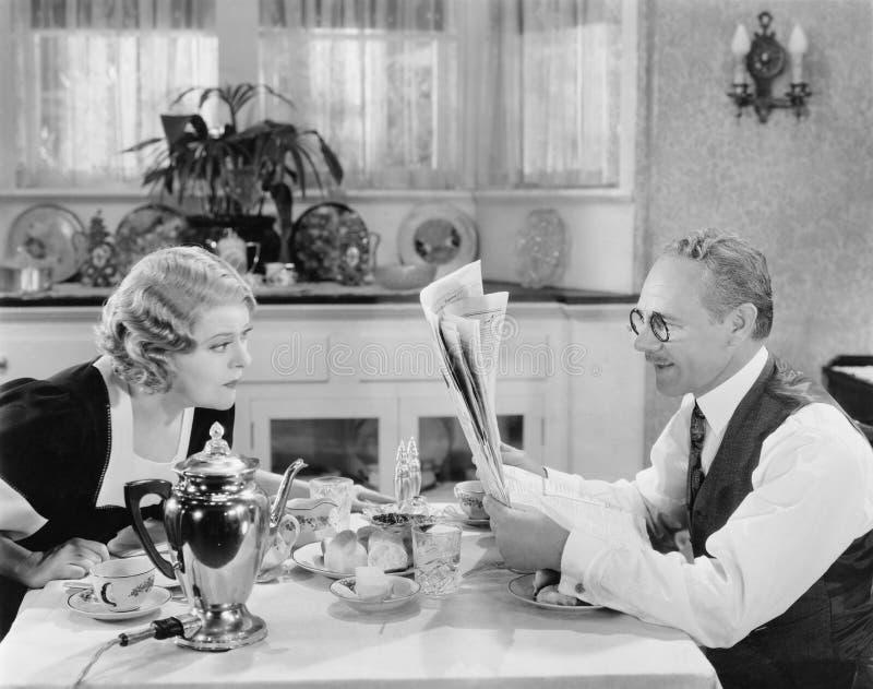 Giornale della lettura delle coppie alla tavola di prima colazione (tutte le persone rappresentate non sono vivente più lungo e n immagini stock