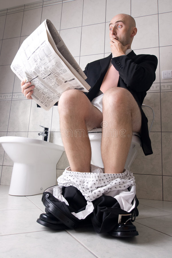 Giornale della lettura sulla toletta fotografie stock libere da diritti