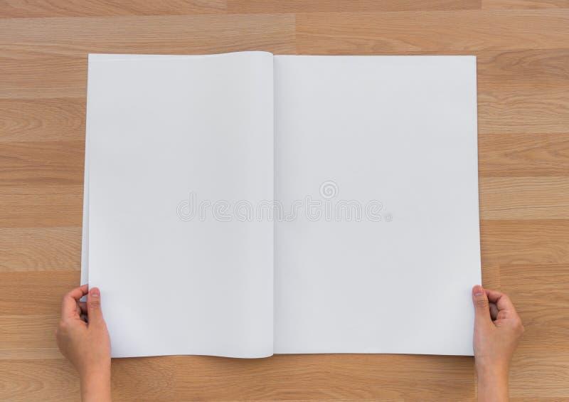 Giornale dello spazio in bianco della tenuta della mano con derisione vuota dello spazio su su backg di legno fotografie stock libere da diritti