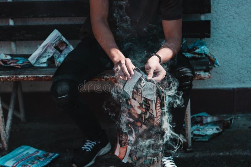 Giornale di fumo in mani mentre sedendosi fotografie stock libere da diritti