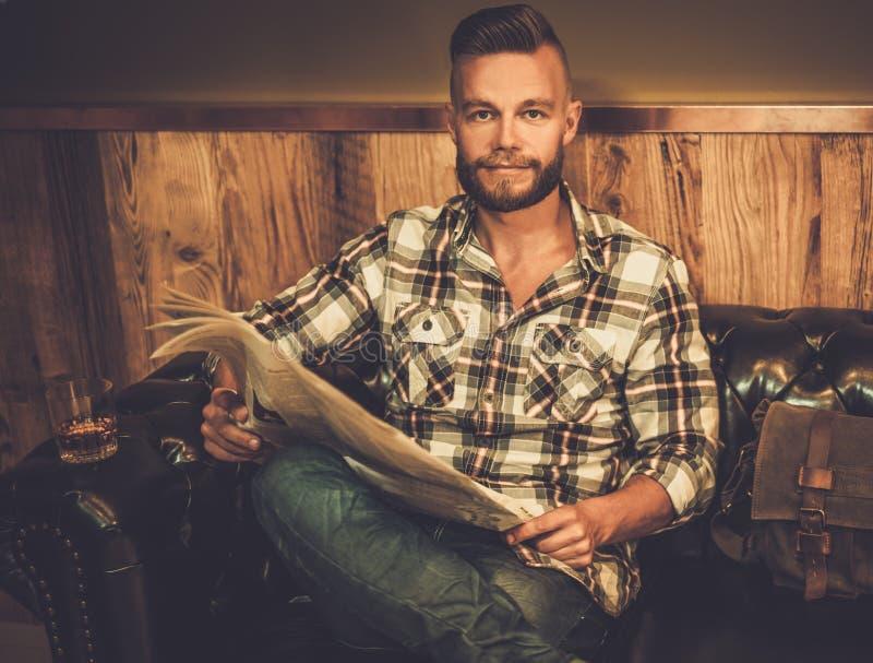 Giornale di mezza età della lettura dei pantaloni a vita bassa nel negozio di barbiere immagine stock