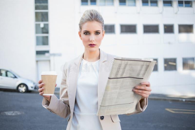 Giornale e caffè alla moda seri della tenuta della donna di affari immagini stock