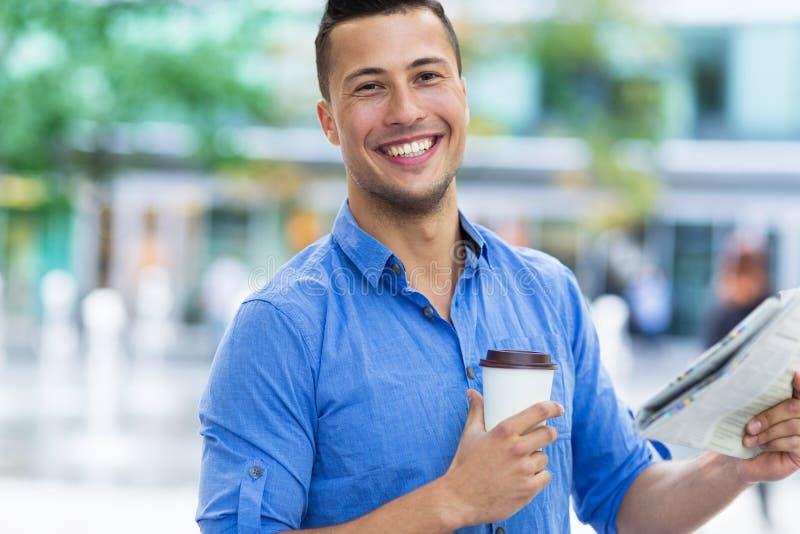 Giornale e caffè della tenuta dell'uomo immagini stock libere da diritti