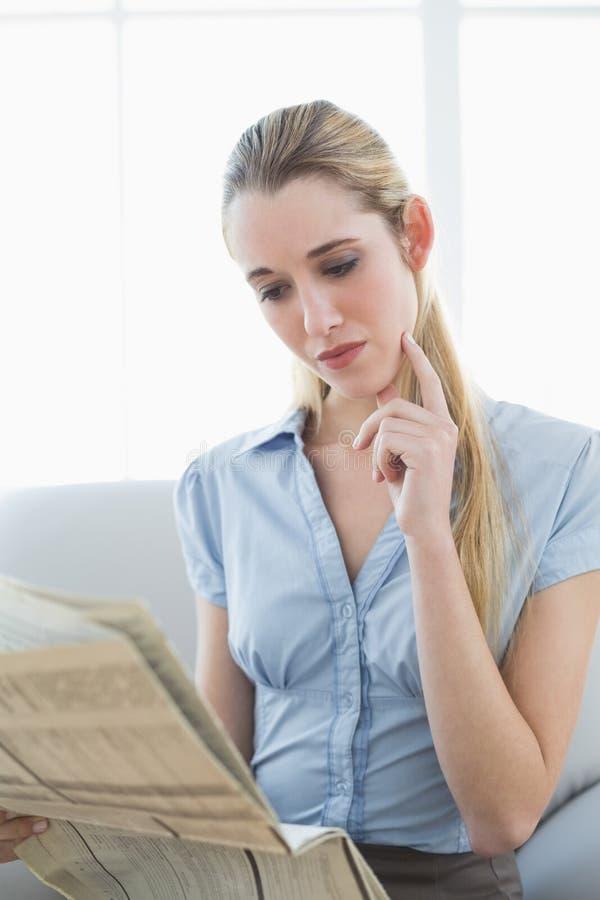 Giornale elegante concentrato della lettura della donna di affari che si siede sullo strato fotografia stock