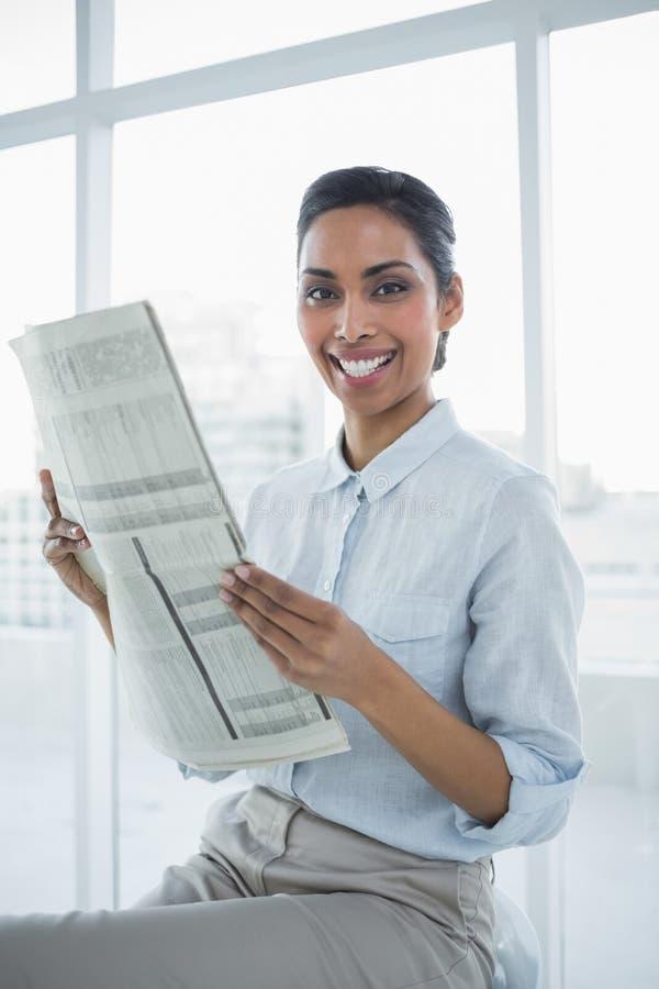 Giornale elegante giulivo della tenuta della donna di affari che sorride alla macchina fotografica fotografie stock libere da diritti