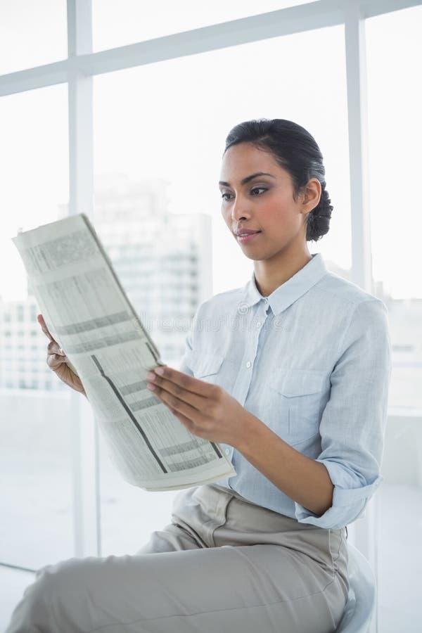 Giornale elegante morbidamente sorridente della lettura della donna di affari immagine stock libera da diritti
