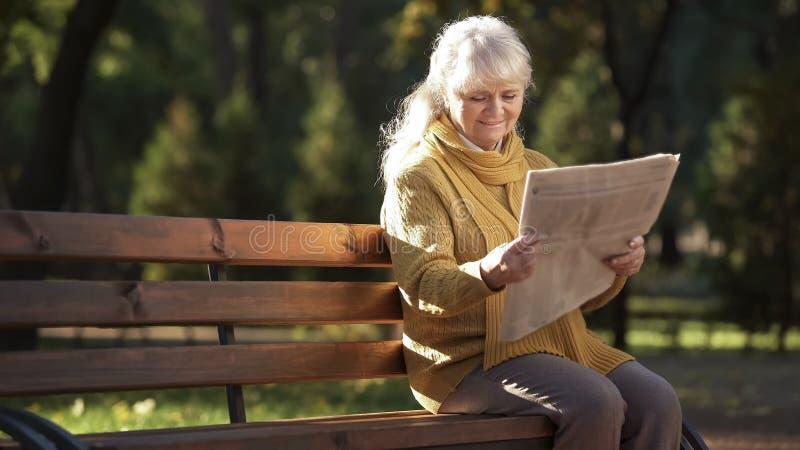 Giornale maturo concentrato della lettura della donna che si siede sul banco in parco, pensionamento immagini stock