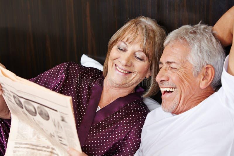 Giornale senior della lettura delle coppie a letto immagini stock libere da diritti