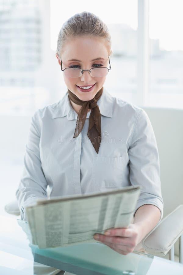 Giornale sorridente biondo della lettura della donna di affari immagini stock