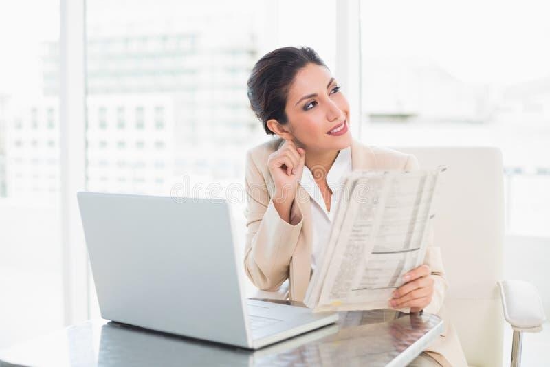 Giornale sorridente della tenuta della donna di affari mentre lavorando al computer portatile fotografia stock