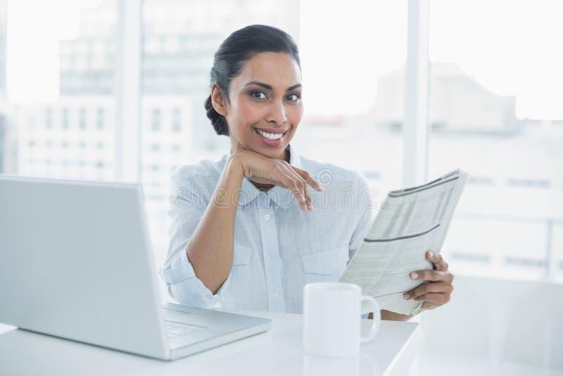 Giornale sorridente sveglio della tenuta della donna di affari che si siede al suo scrittorio fotografie stock