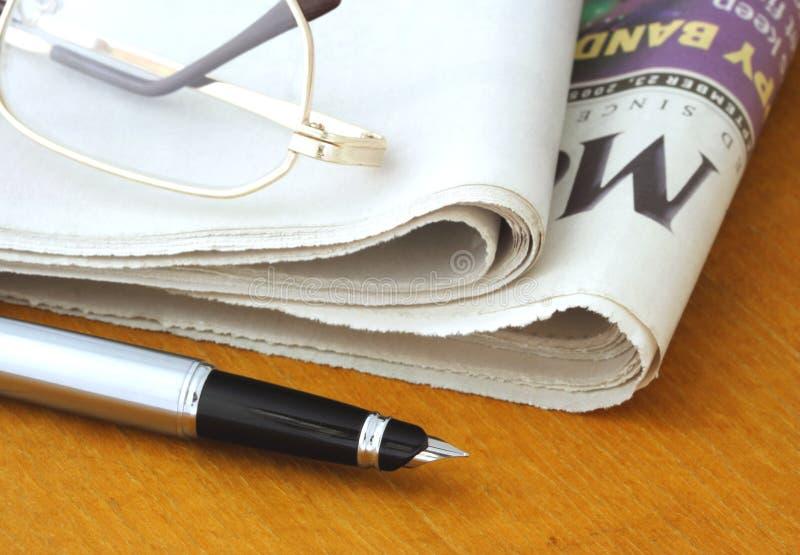 Giornale, vetri e penna fotografie stock libere da diritti