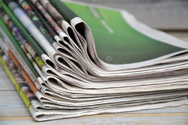 Giornali impilati e su accatastati su un fondo di legno della tavola immagini stock libere da diritti