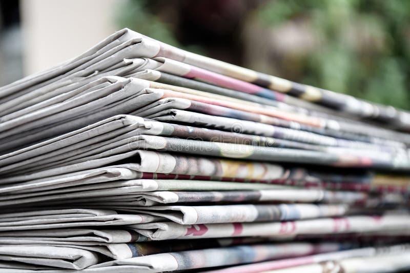 Giornali piegati ed impilati sulla tavola con il fondo di verde di gardenor Immagine del giornale del primo piano e del fuoco sel fotografia stock