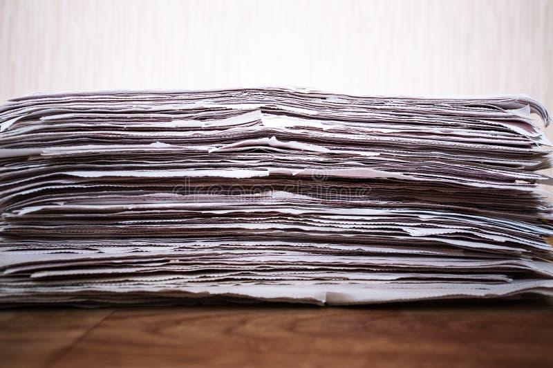 Giornali piegati ed impilati sulla tavola di legno immagine stock