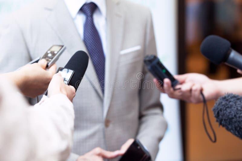 Giornalisti che fanno intervista di media con l'uomo d'affari irriconoscibile o il politico fotografie stock libere da diritti