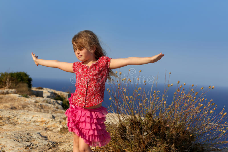 Giorno blu con le mani aperte della ragazza del bambino al vento fotografie stock