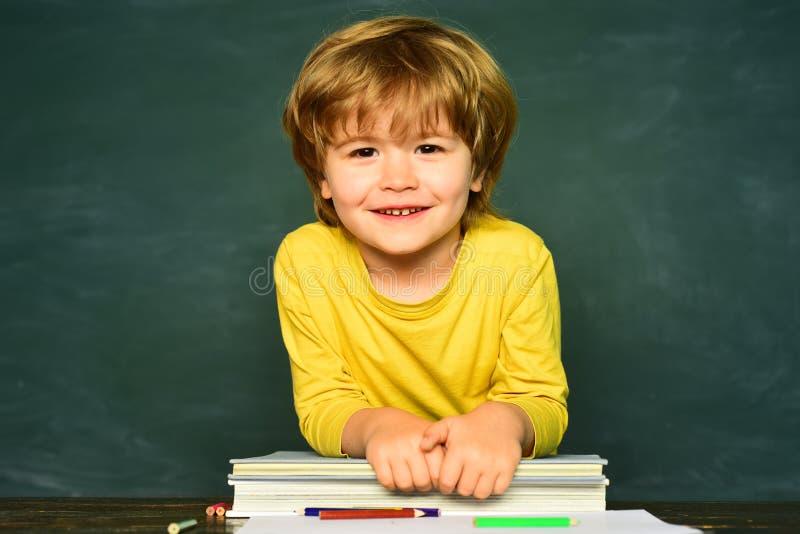 Giorno degli insegnanti Piccolo ragazzo prescolare sveglio del bambino in un'aula Allievi sorridenti felici che disegnano allo sc fotografia stock