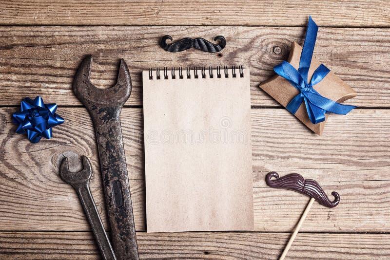 Giorno del padre felice Blocco note in bianco con le chiavi, il regalo ed i baffi su una tavola di legno Grandi e piccole chiavi  fotografia stock libera da diritti
