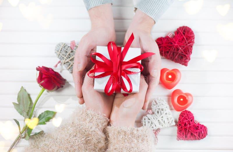 Giorno del `s del biglietto di S La giovane coppia passa il contenitore di regalo della tenuta sopra fondo di legno bianco immagine stock